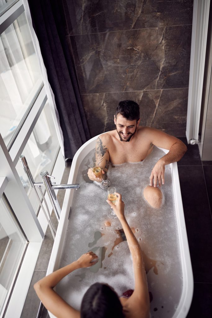 Woman and man taking a bubble bath together while drinking wine