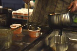 A laddle scoops out some soup from a pot and pours it into a customer's container.