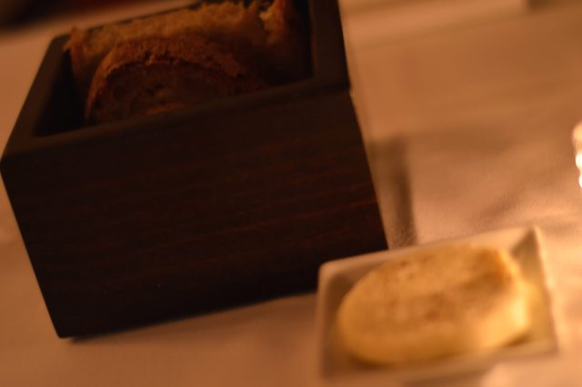 Homemade bread and butter are displayed elegantly on the table.