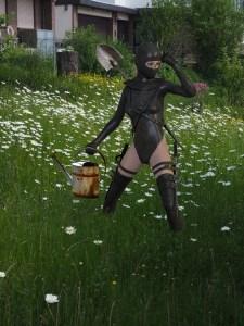 Frau in den Kleidern einer Ninja.Kämpferin aber mit Gieskanne und Spaten im Garten