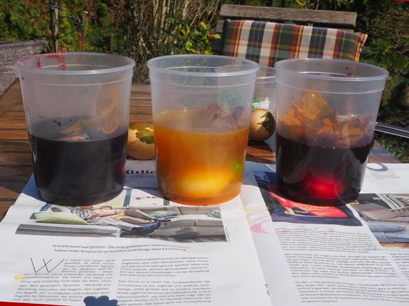 Drei Becher mit je einem Farbsud und zwei Eiern
