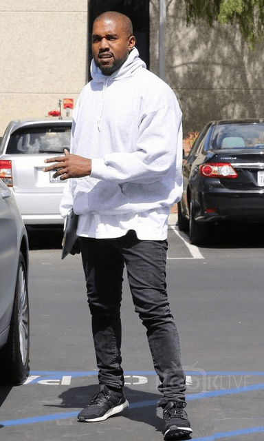 american rapper kanye west pictured wearing a black adidas ultra boost with black skinny jeans and a