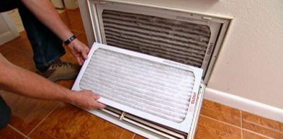 Changing air conditioner air filter.