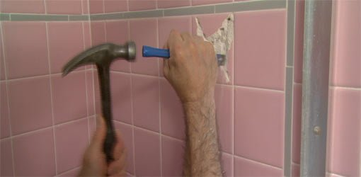 Using a cold chisel and hammer to remove a ceramic tile.