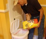 Joe Truini pouring kitty litter into garbage can bag