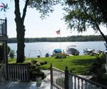Photo of lawn leading to lake with boats.