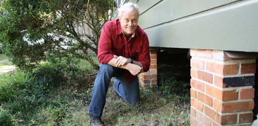 Danny Lipford inspecting for termites under a house.