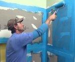 Applying waterproofing sealer to cement backer board before tiling.
