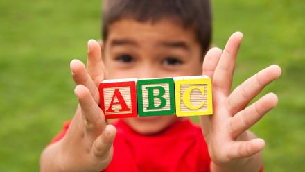 kid holding ABC wooden blocks