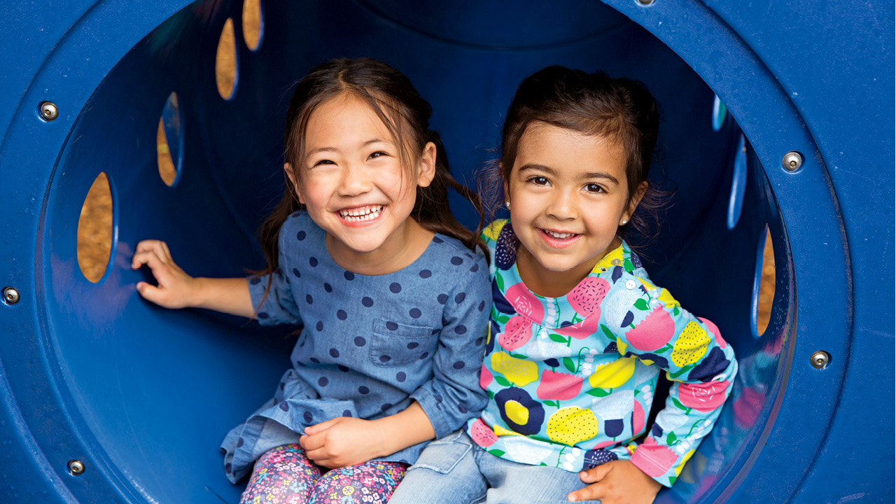 two little girls sitting together in a blue tube at the park for a story on milestone development