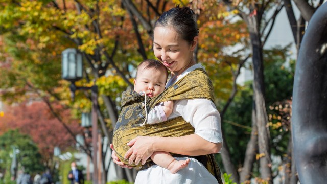 A photo of a parent in a white shirt wearing a green and grey patterned Didyklick with their baby inside. They are outside with yellow and orange leafed trees in the background.