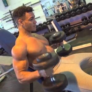 Hombre trabajando bíceps con mancuernas sentado (gym)