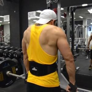 Hombre entrenando trapecio con barra en gym