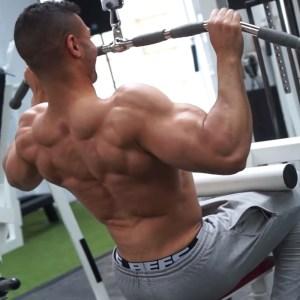 Hombre trabajando espalda con polea alta en gym