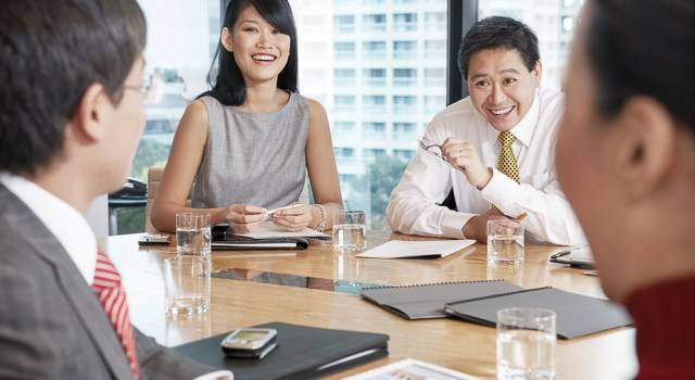 Young Asian business people having discussion in boardroom