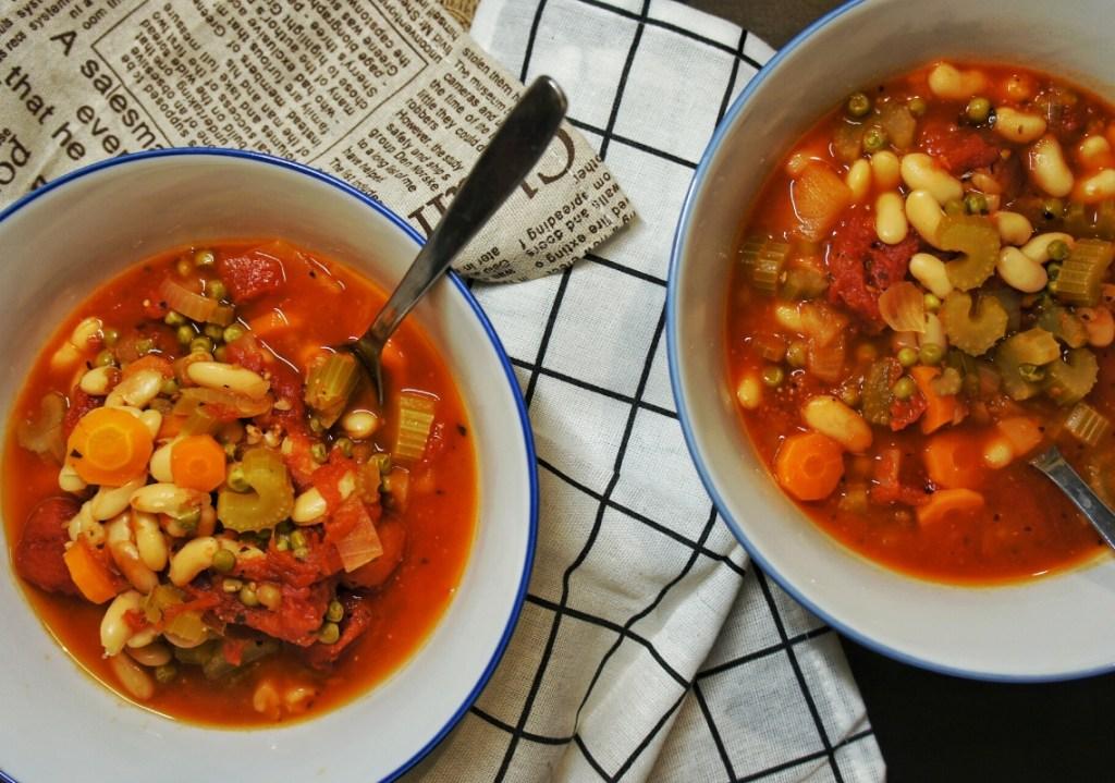Focus of two bowls of white bean tomato soup