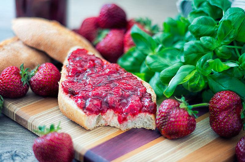 Abbildung von Erdbeermarmelade mit Basilikum auf einem Brötchen
