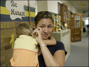 Amy Blair, holding her daughter, Isabella, 4, wipes away a tear after seeing her son, Connor, 6, off to his first day in kindergarten at Eagle Point Elementary School in Rossford.