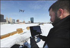 Phil Myers, a co-founder and primary pilot for Toledo Aerial Media, flies a DJI Inspire 1 drone over the Maumee River. The drone can record stills and video with its on-board camera and can stay airborne 15 to 20 minutes on one charge.