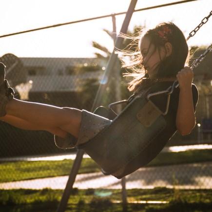 backlit girl on swing