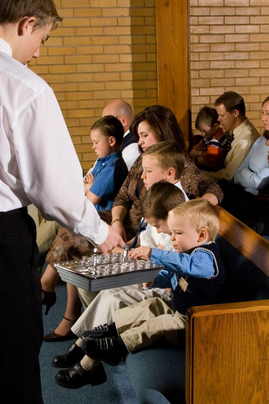 family with young kids sitting reverently during the sacrament