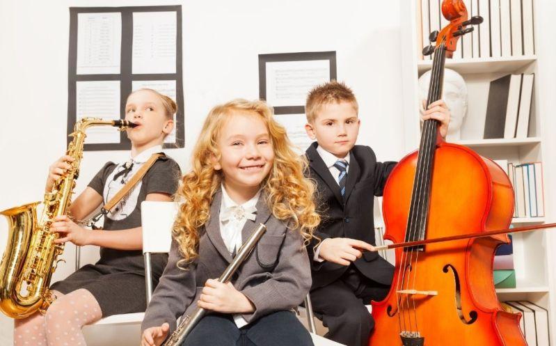 Tre børn med musikinstrumenter. Smilende pige i forgrunden