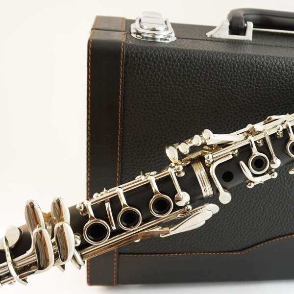 Produktbillede af klarinet med instrumentkasse i baggrunden