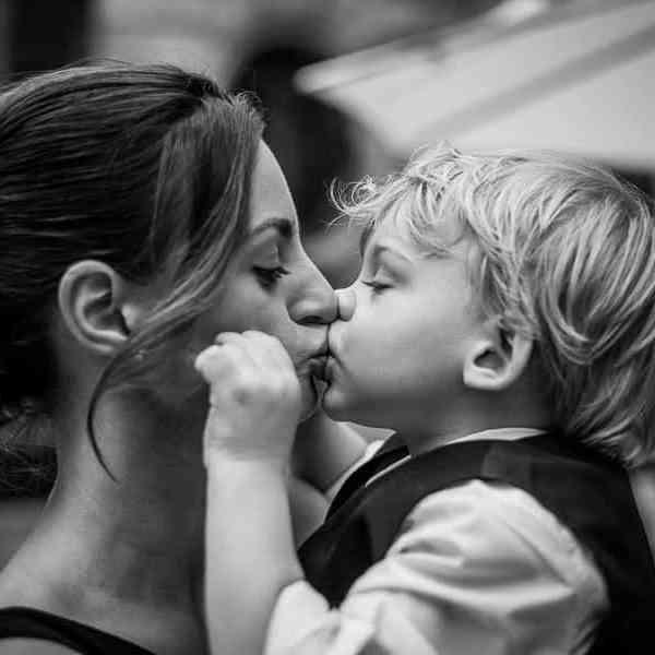 Photo prise sur le vif un enfant faisant un bisou à sa maman sur la bouche