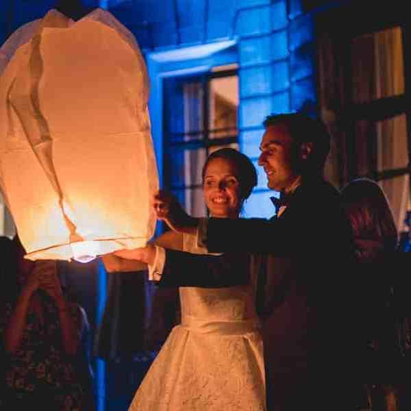 Pendant la soirée de mariage un lancer de lanterne avec le couple de mariés couleurs chaudes