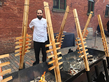 large pieces of salmon held in wooden presses angled towards open fires on a brick pavement by a brick building, and a chef standing by them