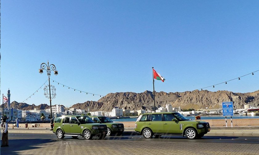 Queen Elizabeth waves from front Sultan Qaboos Range Rover on way to the Palace in Muscat