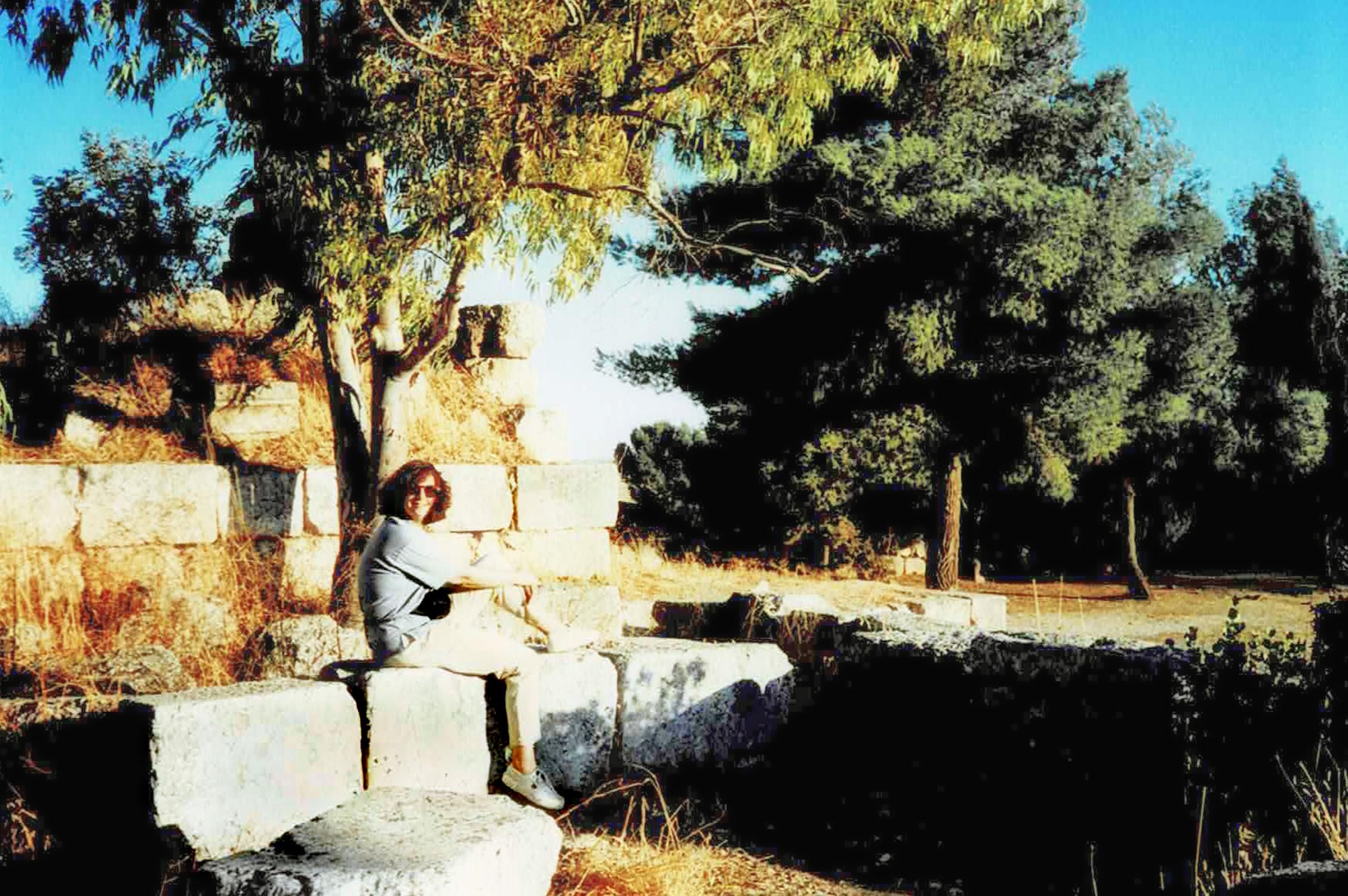 Woman sitting among ruins and pine trees