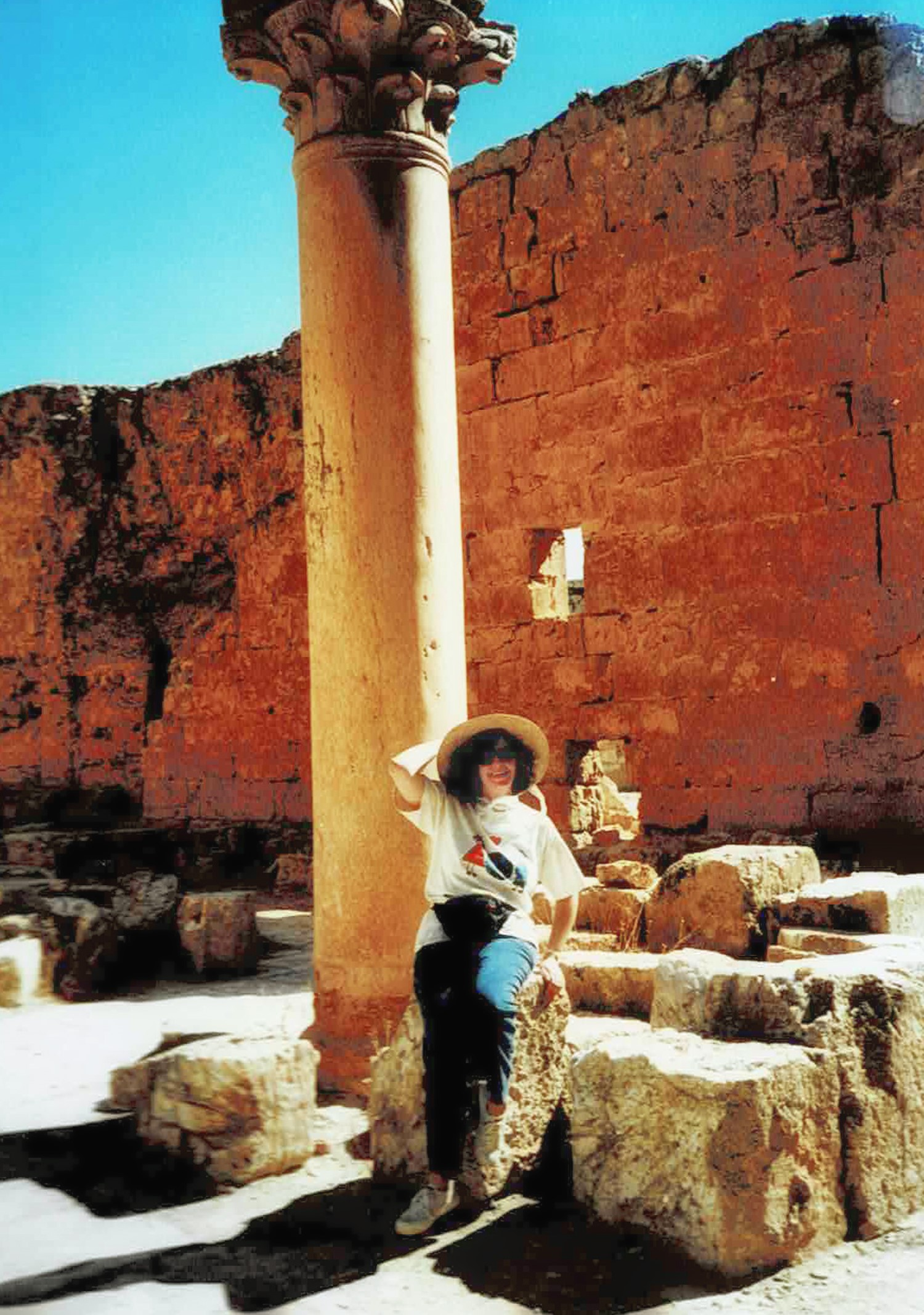 Woman in a hat in front of a column