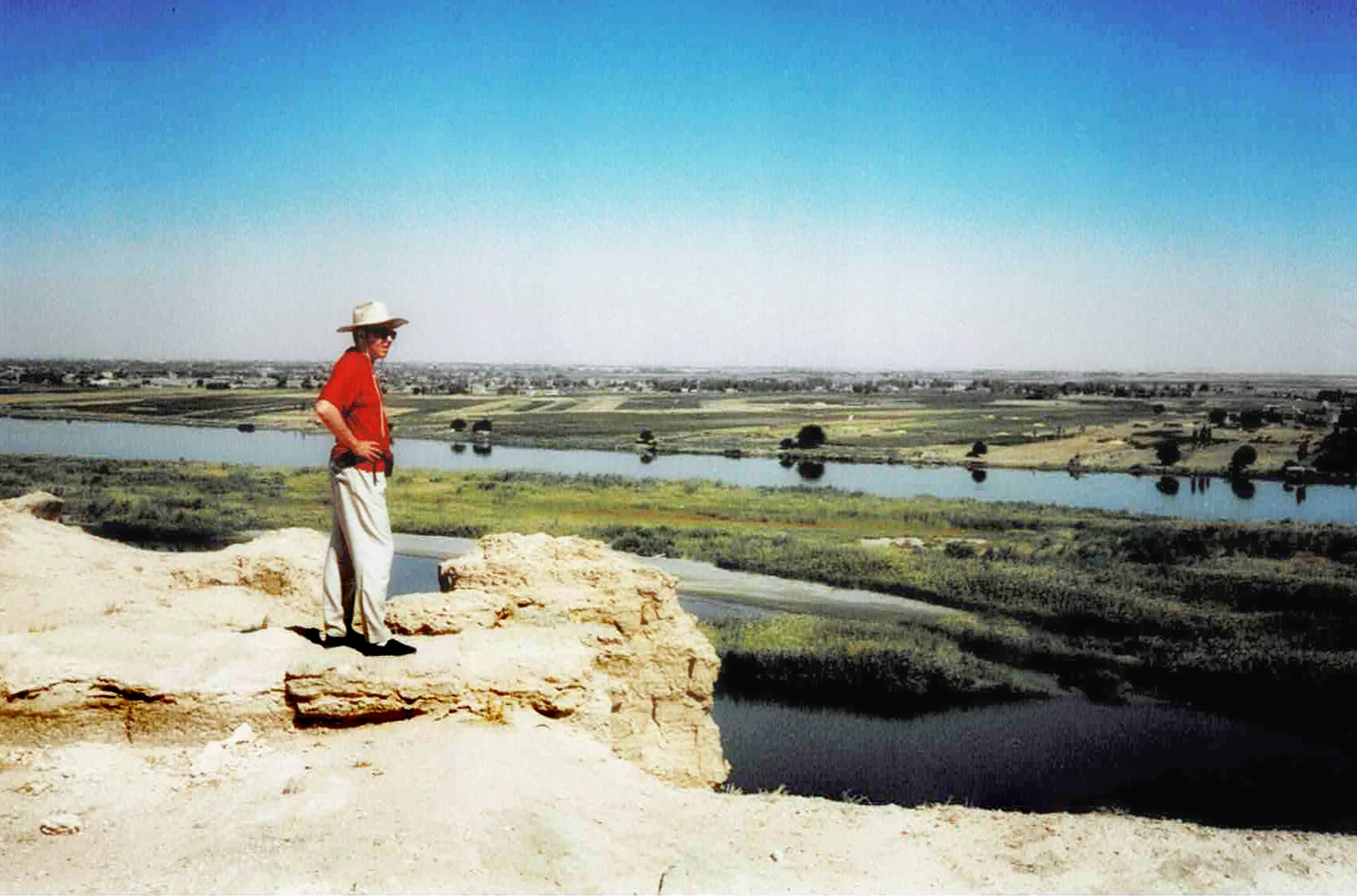 Man on a stony outcrop overlooking a river