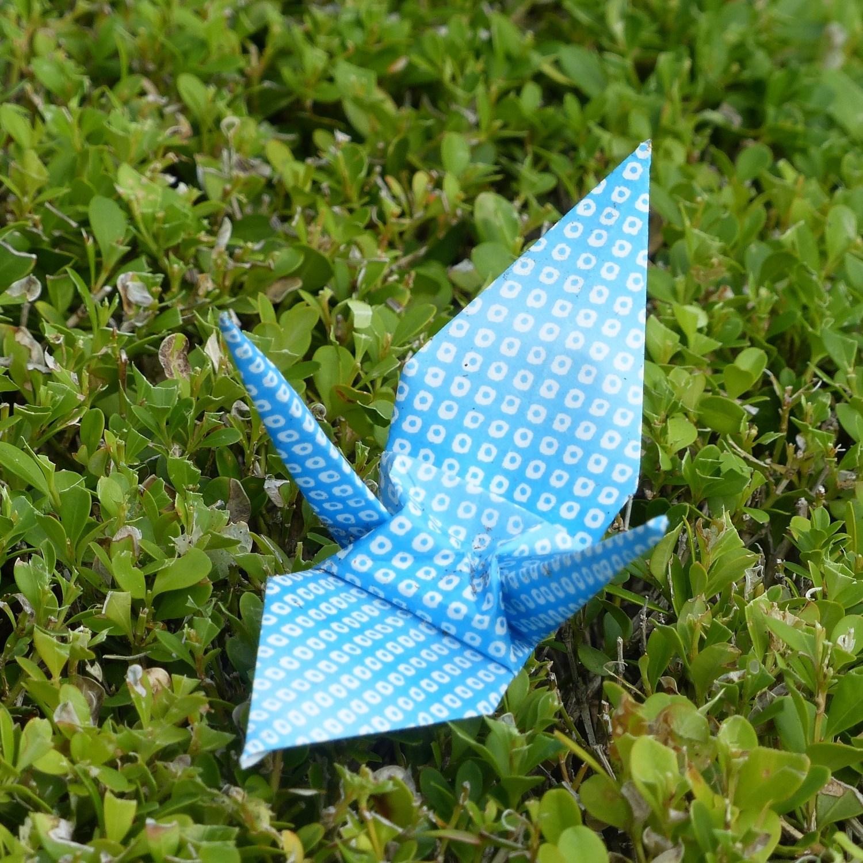 Paper crane on a hedge