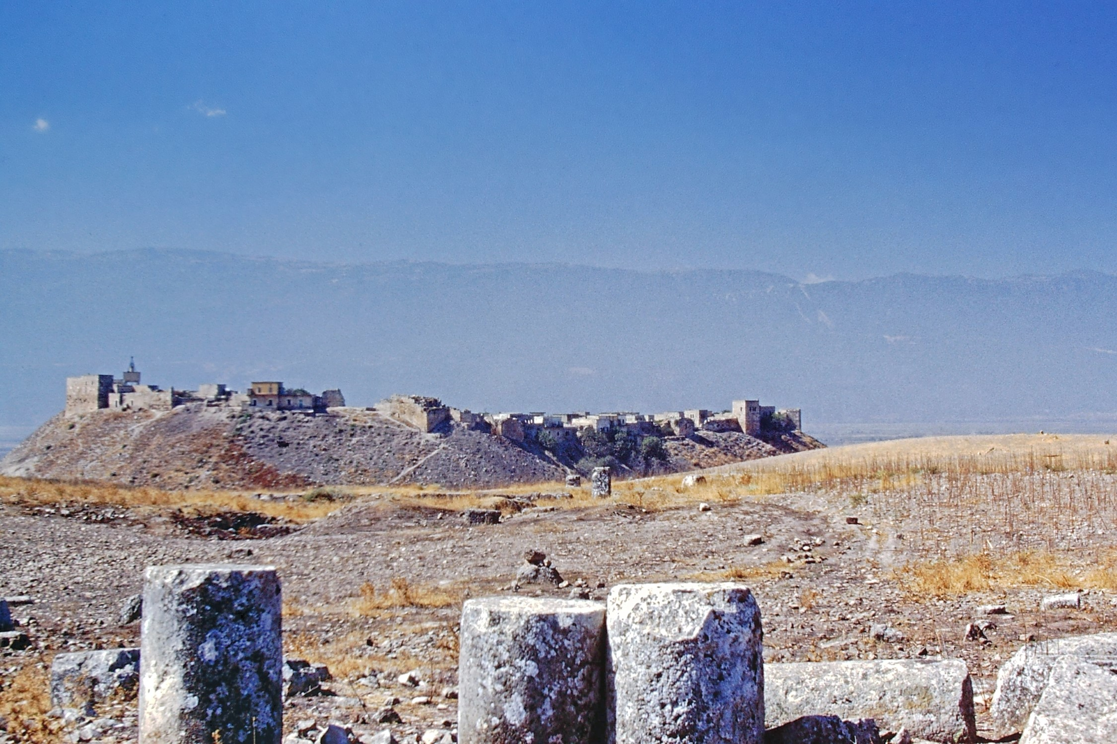 Ruined columns and a distant village
