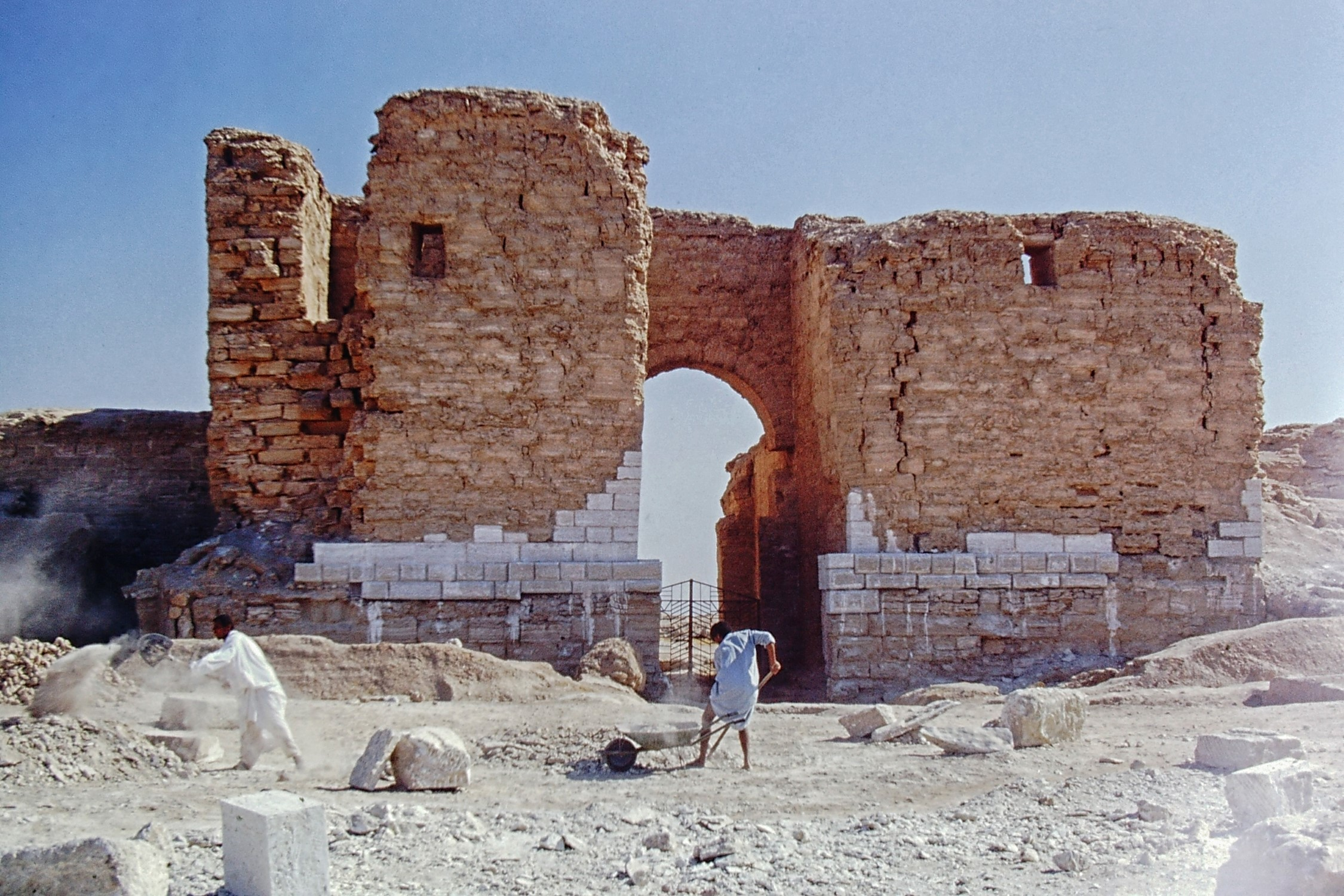 Workmen in front of ruined arch