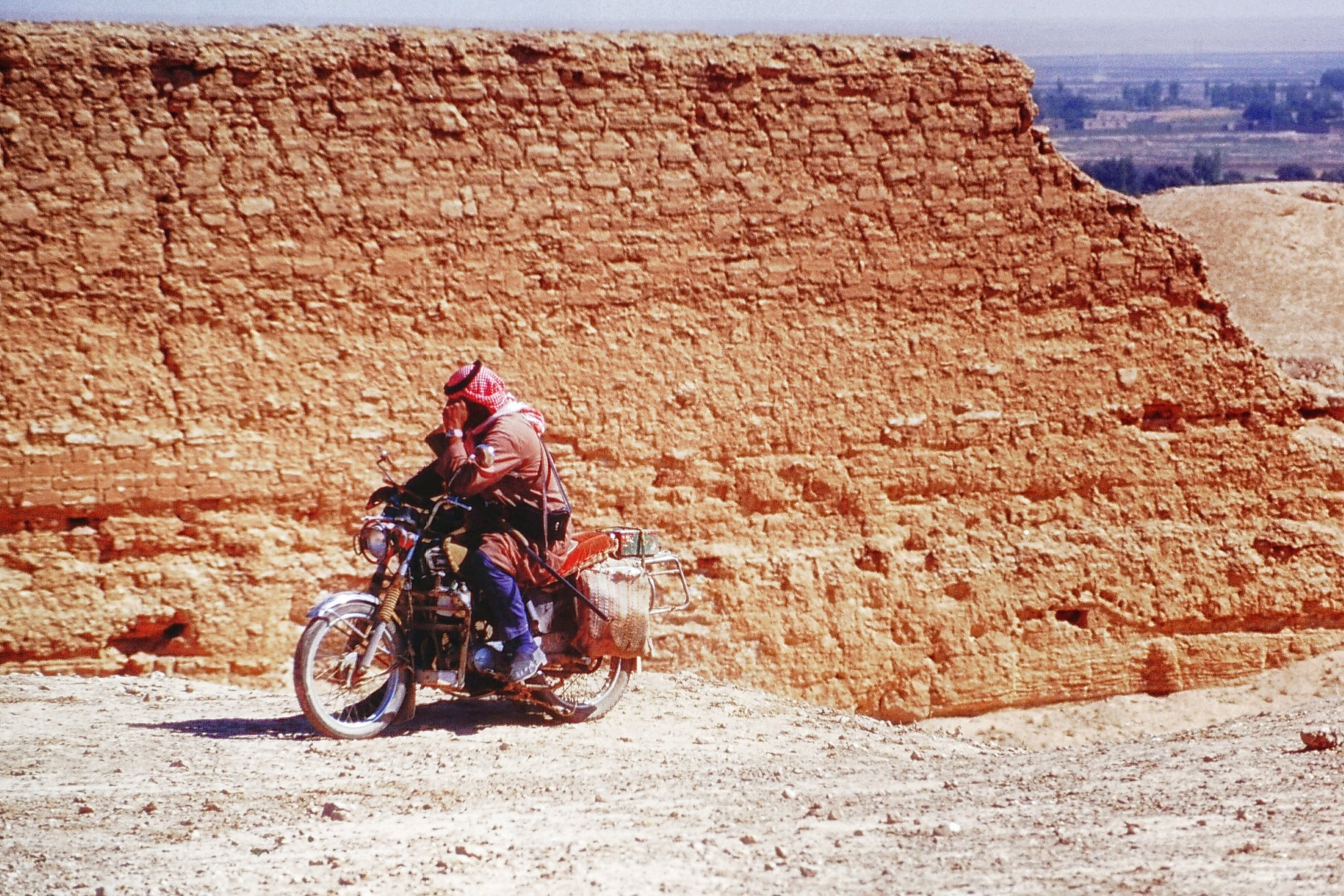 Man on a motorbike by a ruined wall
