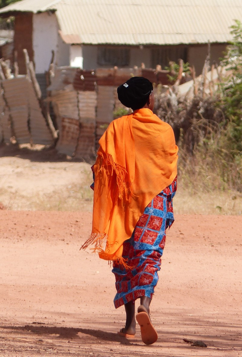 Woman in bright clothes on a dusty street