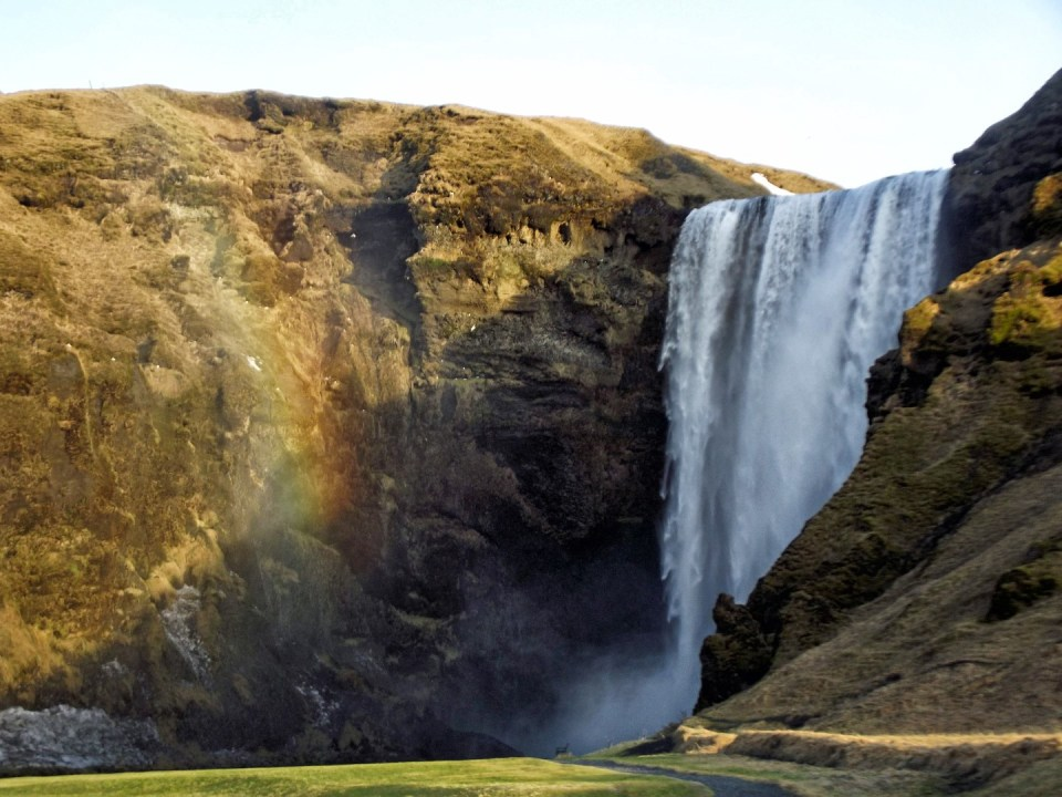 Large waterfall with rainbow in the spray