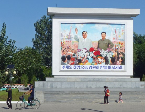 Large mosaic of Kim Il Sung and Kim Jong Il with people bringing flowers
