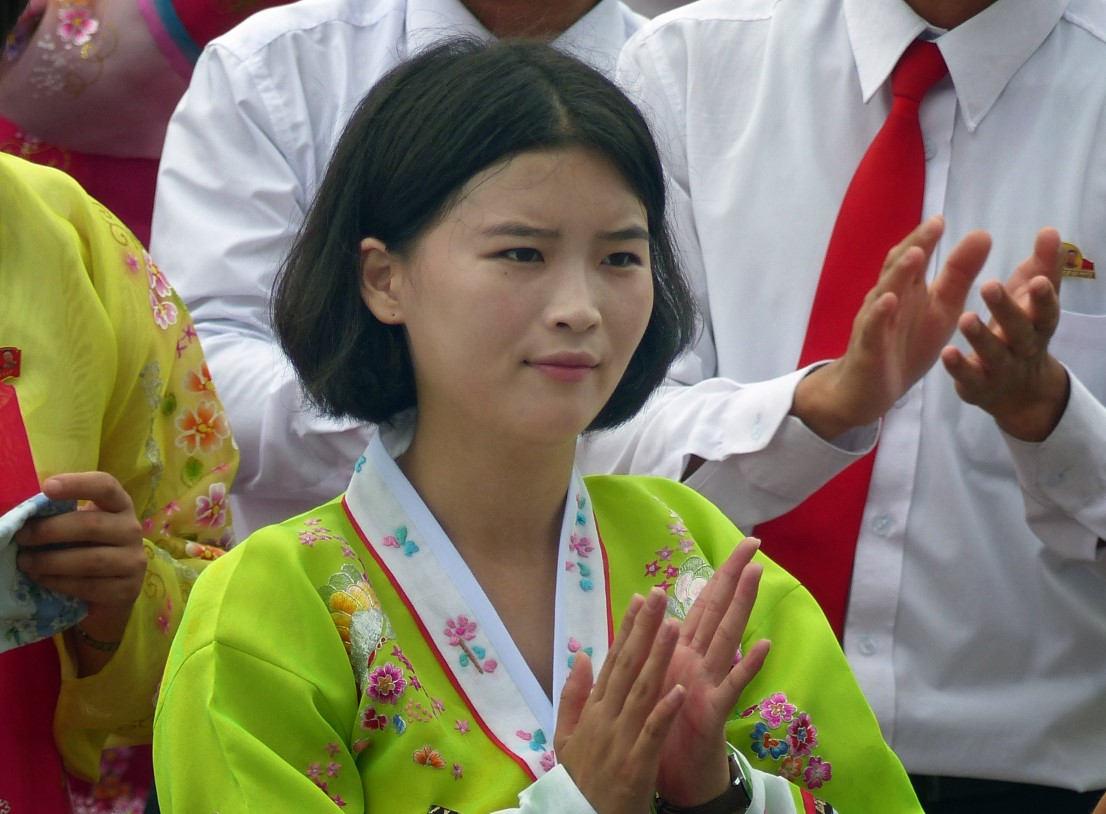 Girl in traditional Korean dress clapping