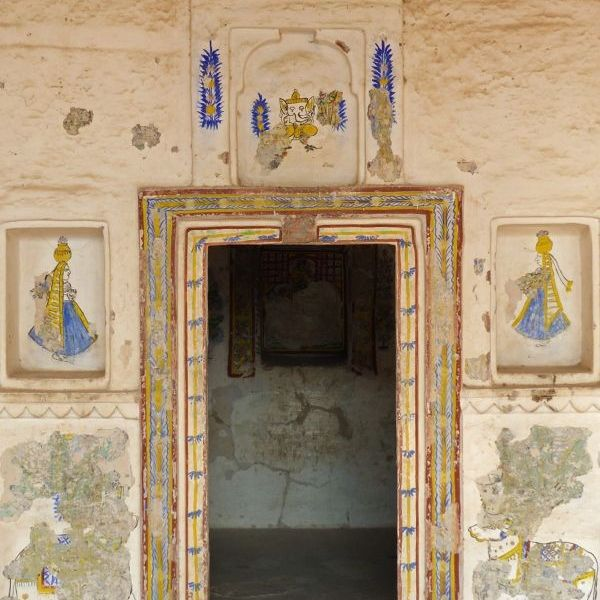 Stone wall with doorway and wall paintings