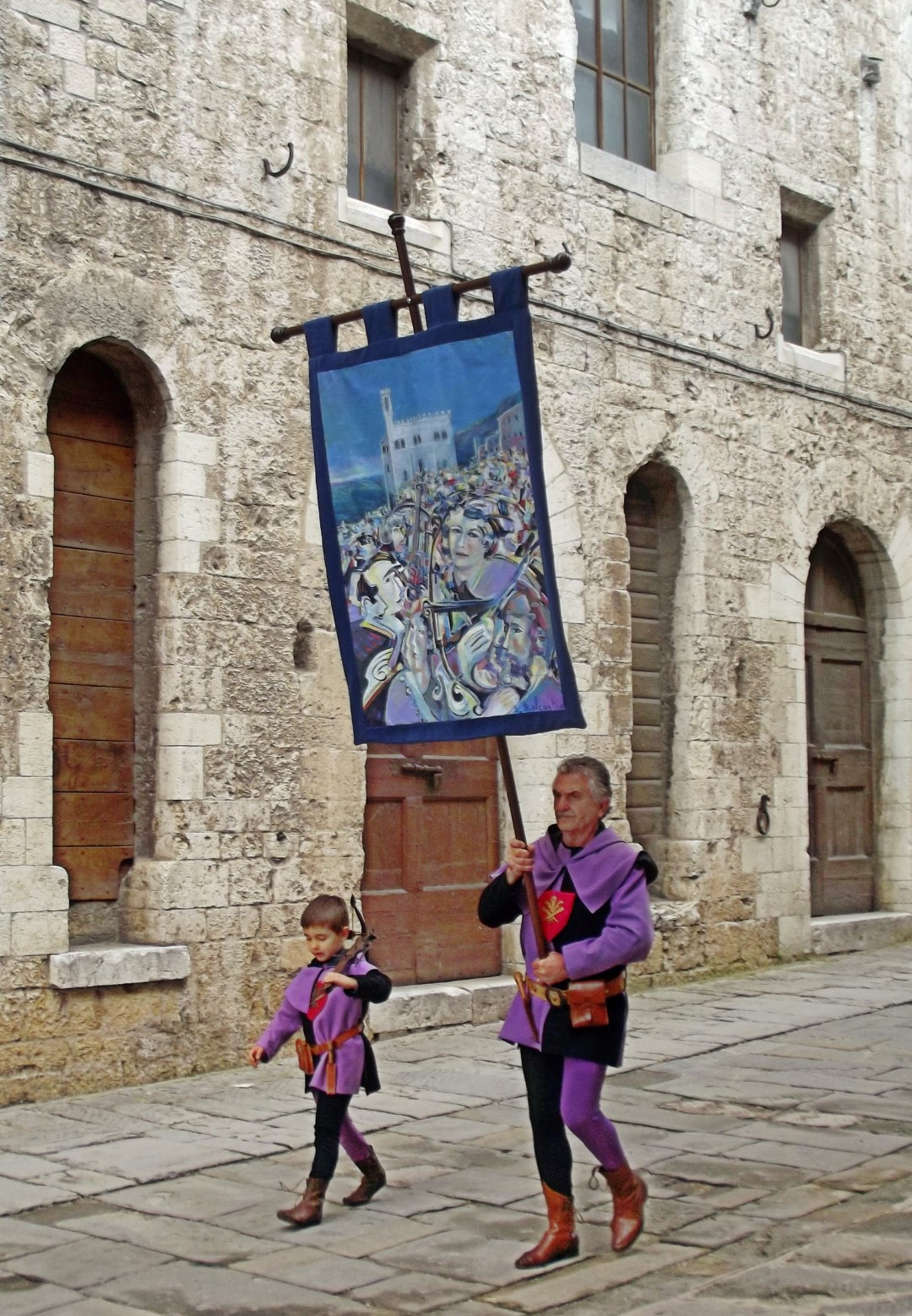 Man and young boy in purple and black with banner