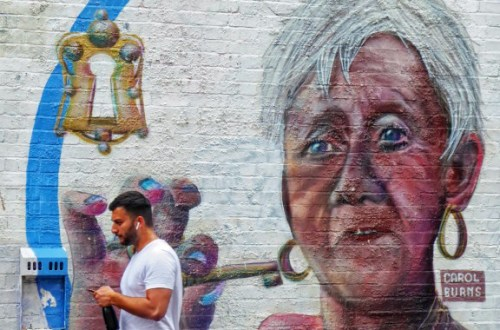Man walking past wall with mural