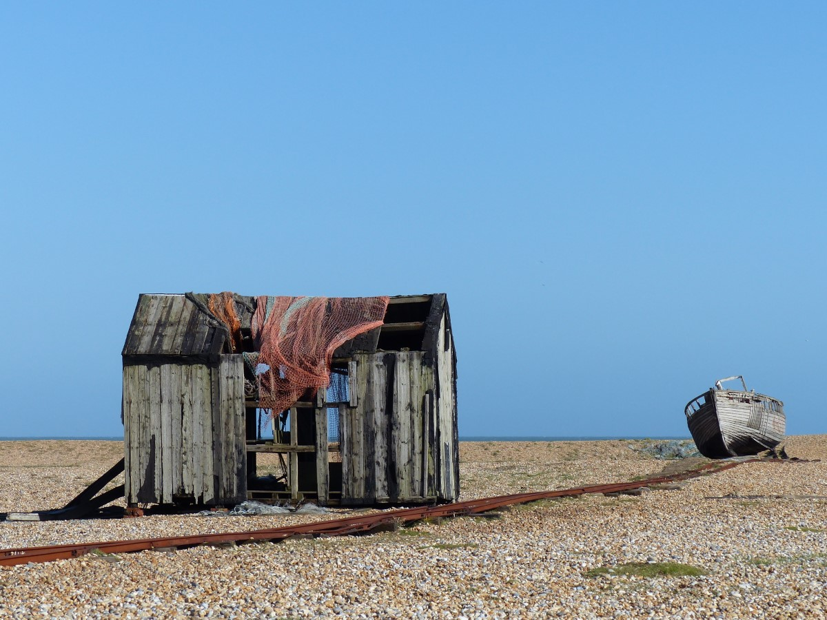 Battered shed and boat on a shingle beach