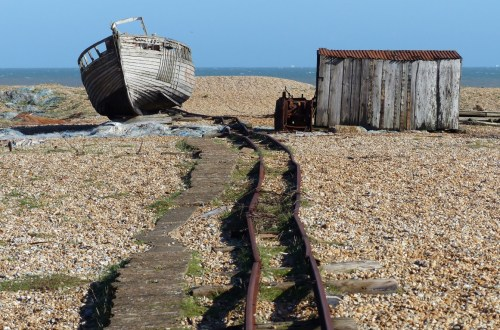 Old boat and rail track on a shingle beach