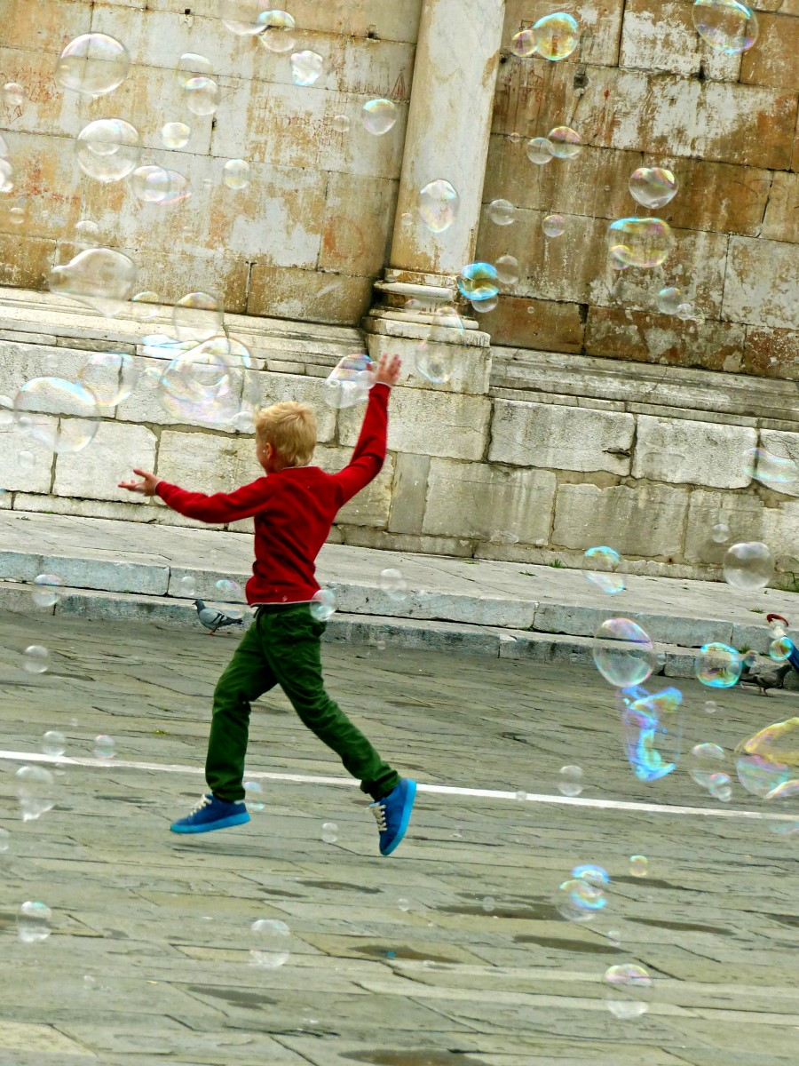 Boy in red jumper dancing with bubbles