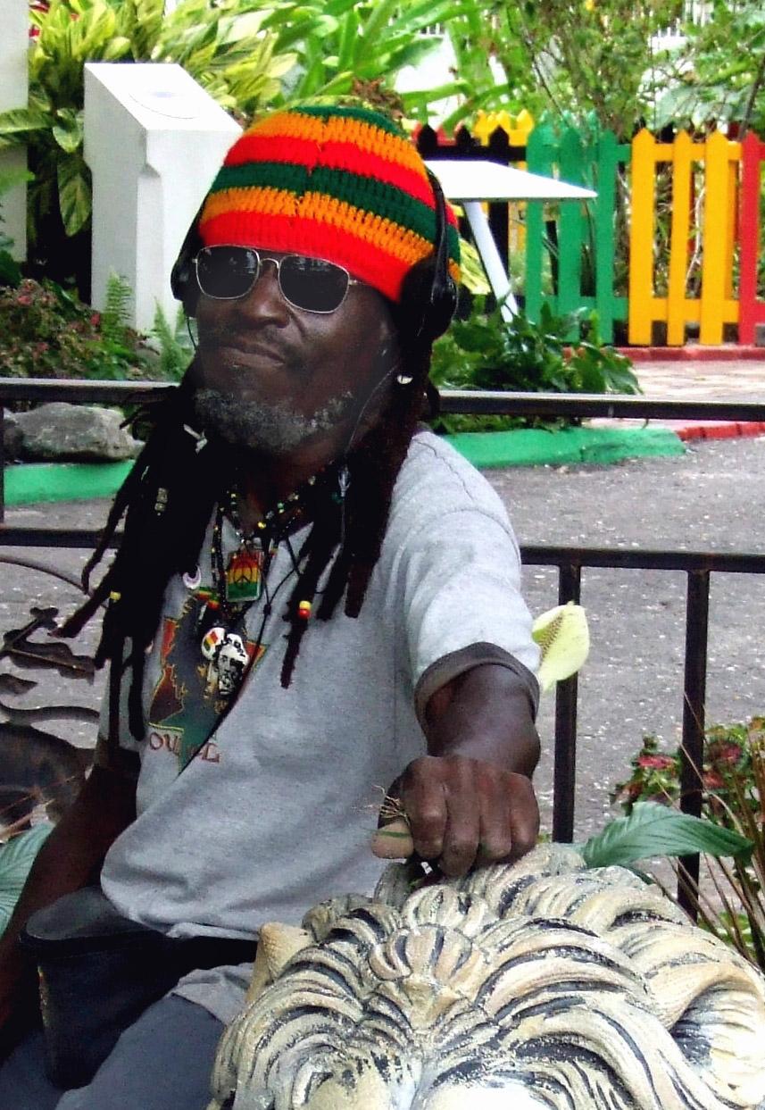 Man in rasta hat leaning on stone lion