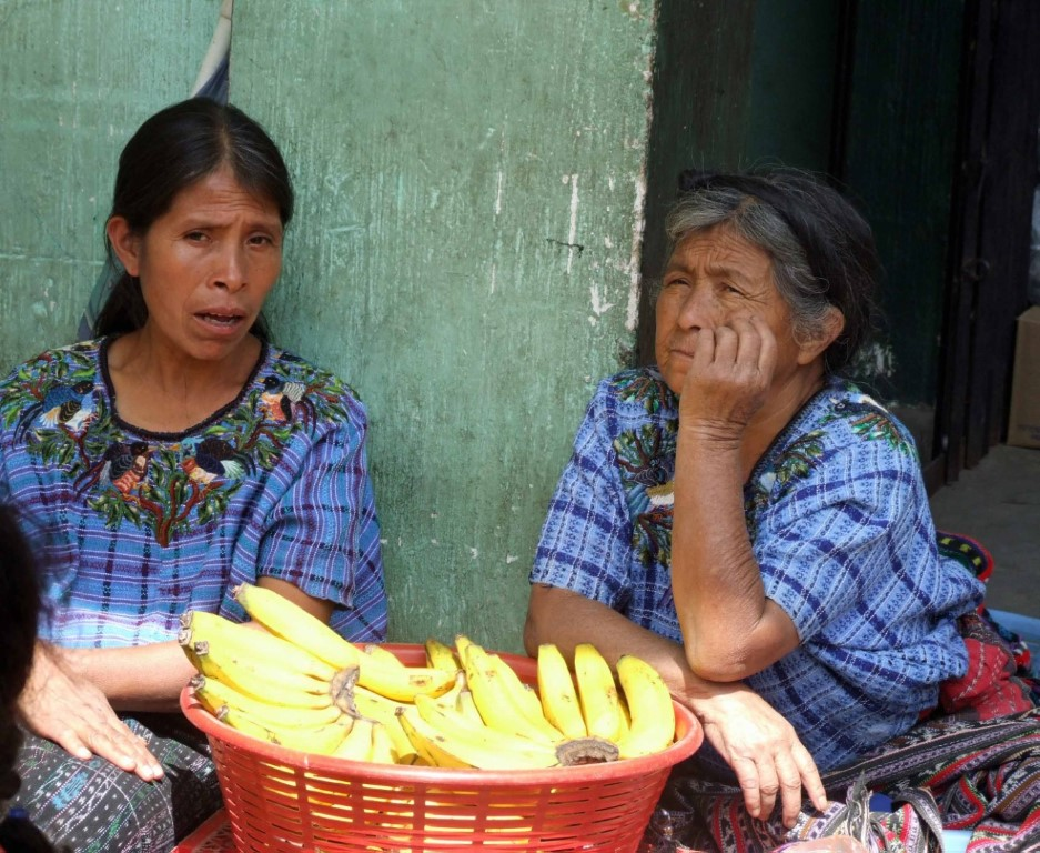 Two women in blue blouses selling bananas